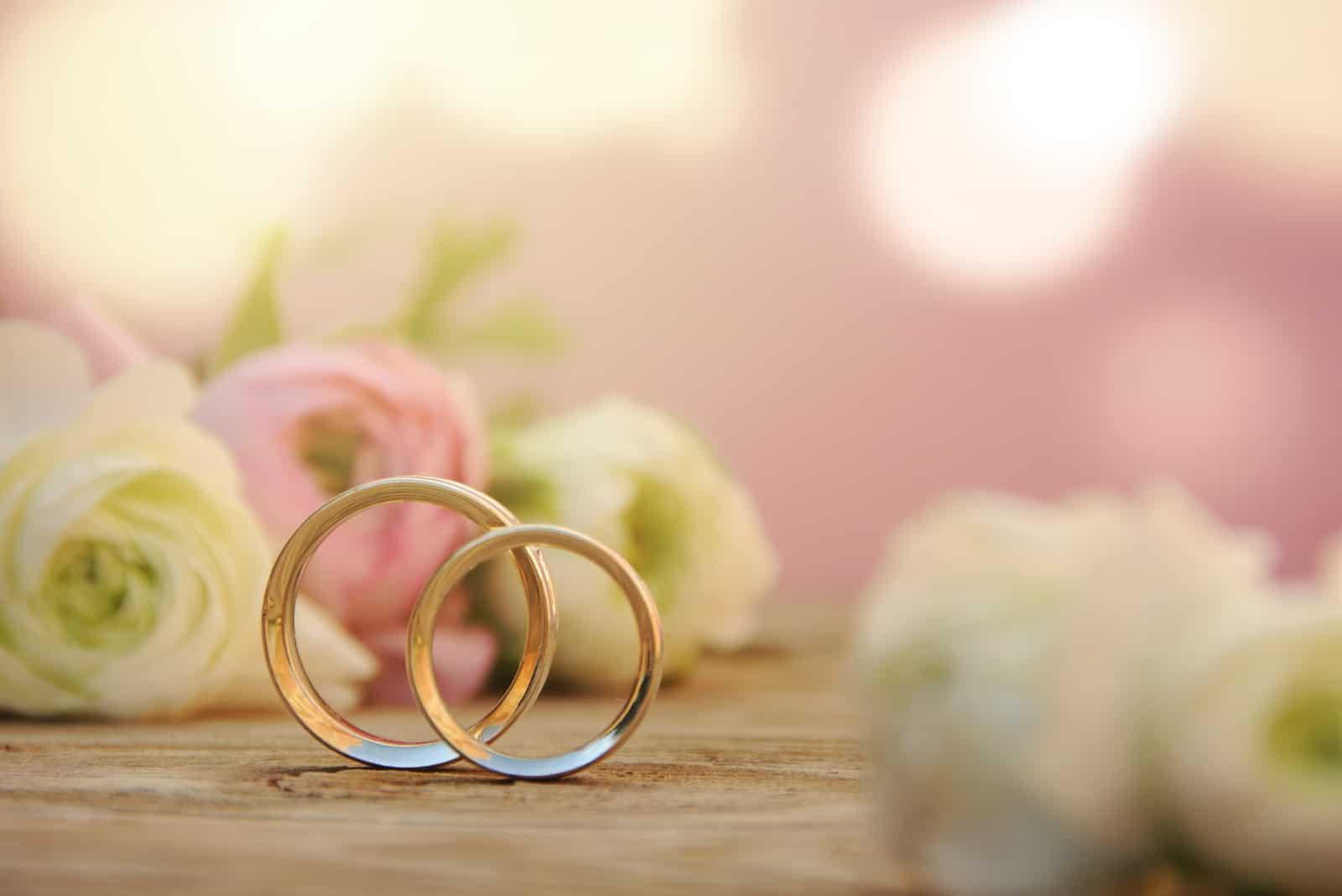 Zarter Hochzeitshintergrund mit Ringen und Butterblumenblume