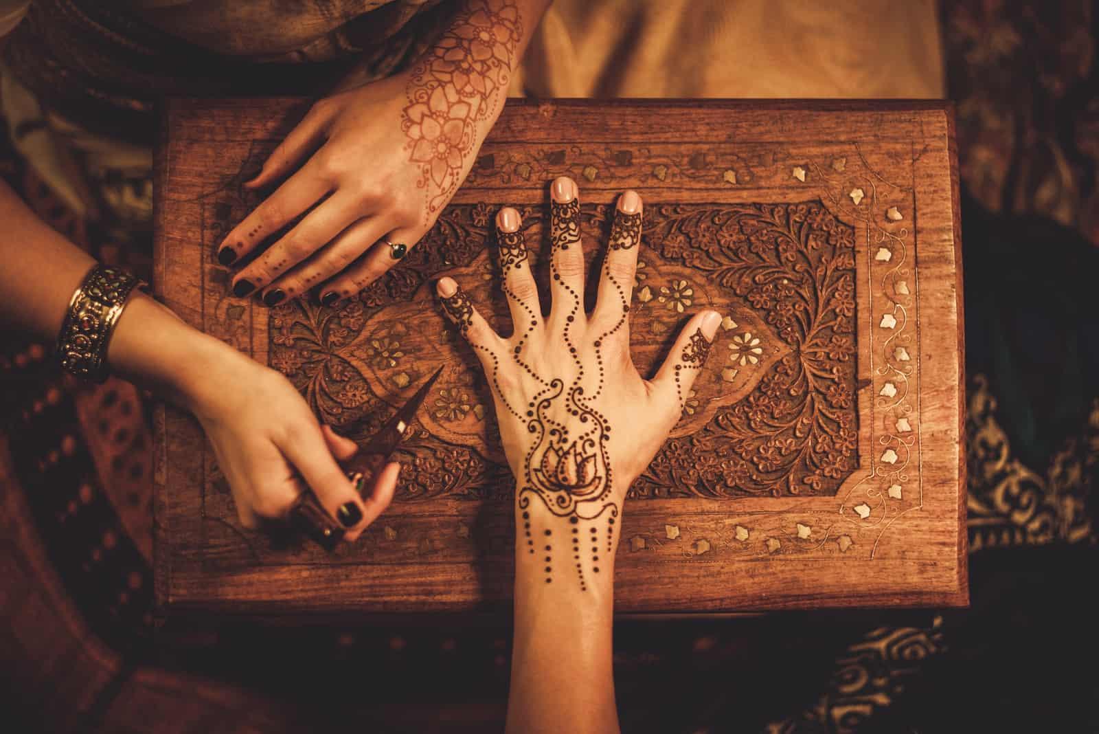 Zeichenprozess der Henna-Menhdi-Verzierung auf der Hand der Frau