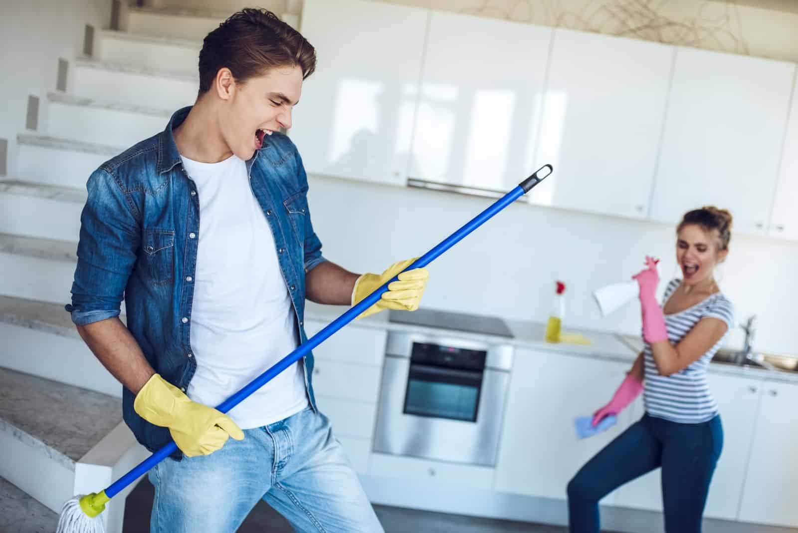 Zwei junge Leute haben Spaß beim Putzen des Hauses