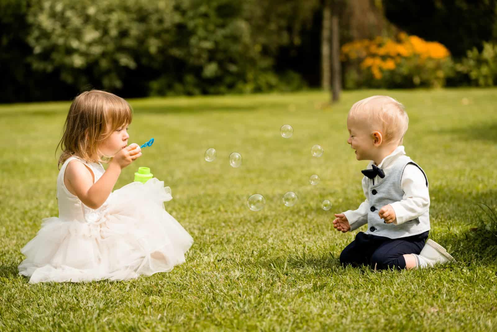 Zwei kleine Kinder spielen im Gras