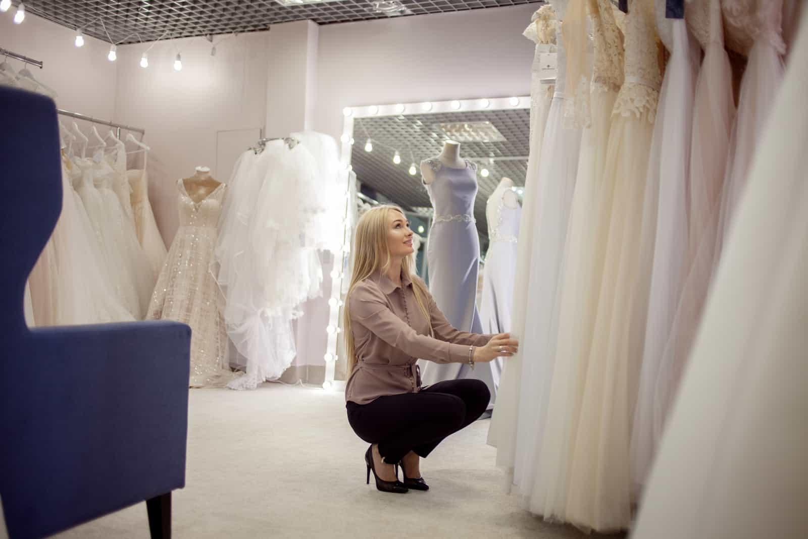 blonde Frau wählt ein Hochzeitskleid