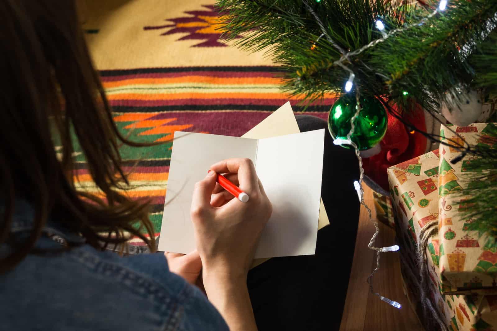 ein Mädchen, das eine Grußkarte schreibt, während es auf dem Boden sitzt