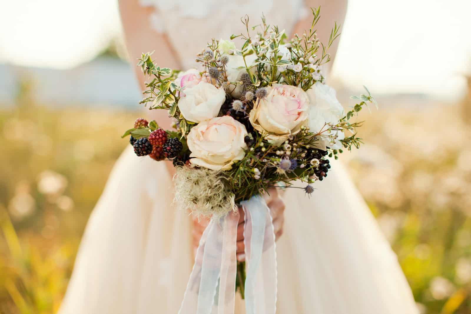 ein Strauß Waldfrüchte und weiße Rosen
