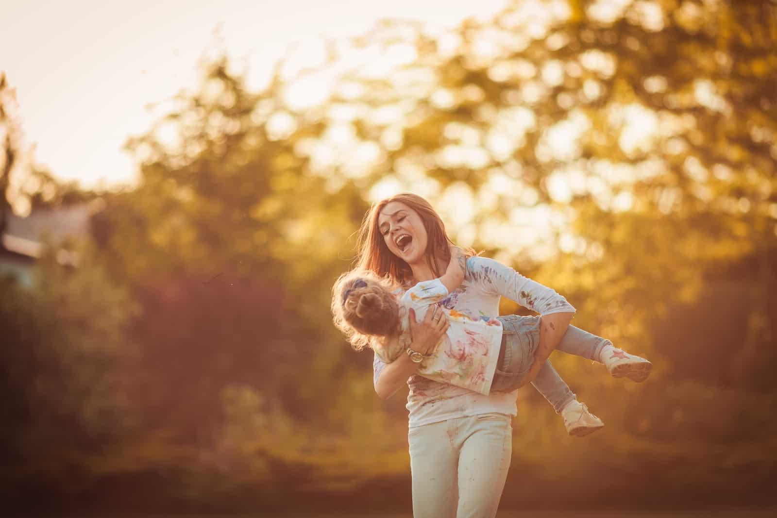 ein lächelndes Mädchen, das ein kleines Kind in ihren Armen hält