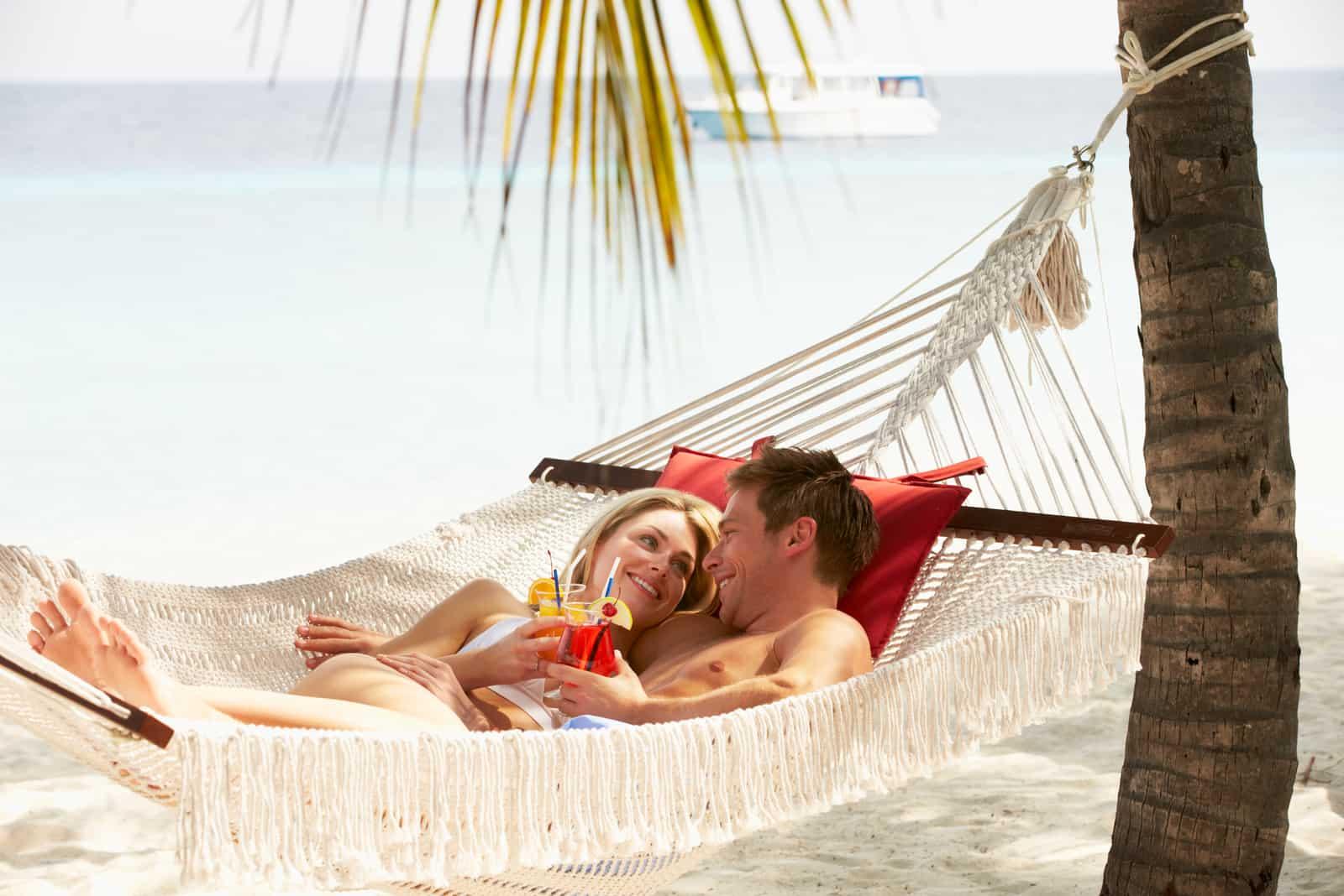 ein liebendes Paar, das in einer Schaukel am Strand liegt