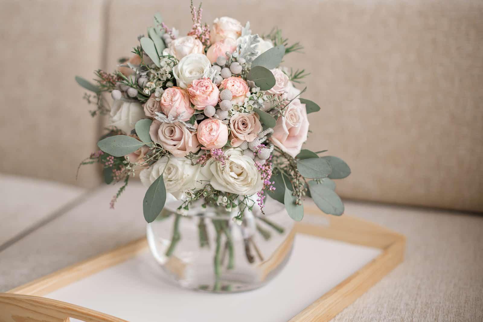 ein schöner Hochzeitsstrauß von Rosen in einer Vase auf dem Tisch
