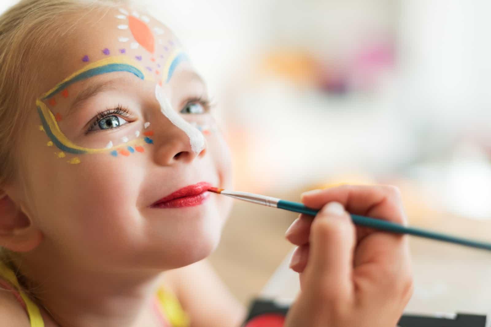 eine Person, die Schmetterlinge auf das Gesicht eines Mädchens zeichnet