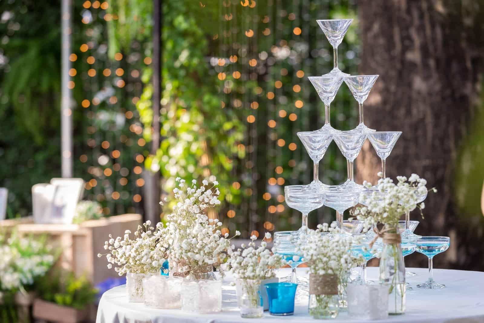 eine Pyramide von Champagnergläsern bei einer Hochzeit im Garten
