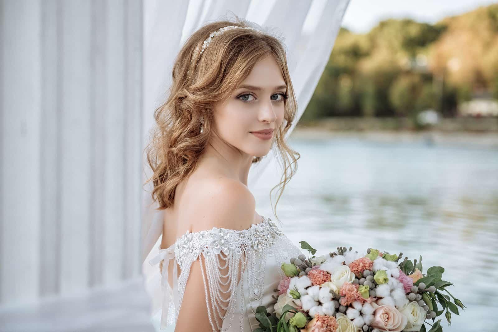eine schöne Braut mit einem großen Blumenstrauß
