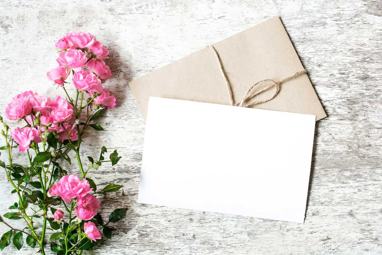 weiße Grußkarte und Umschlag mit rosa Rosenblüten