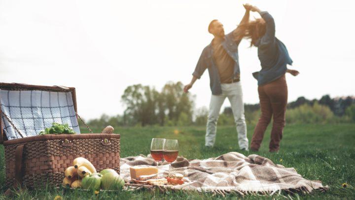 ein liebevolles Paar, das bei einem Picknick in der Natur tanzt