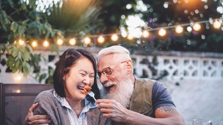 Beim Abendessen im Garten hat ein älteres Ehepaar Spaß