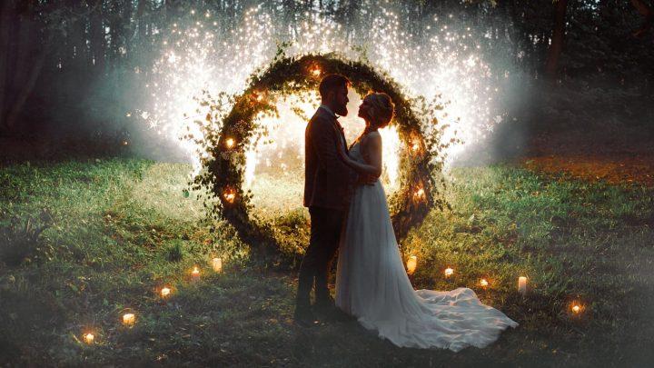 Das Brautpaar im Park umarmt sich neben dem Kranz