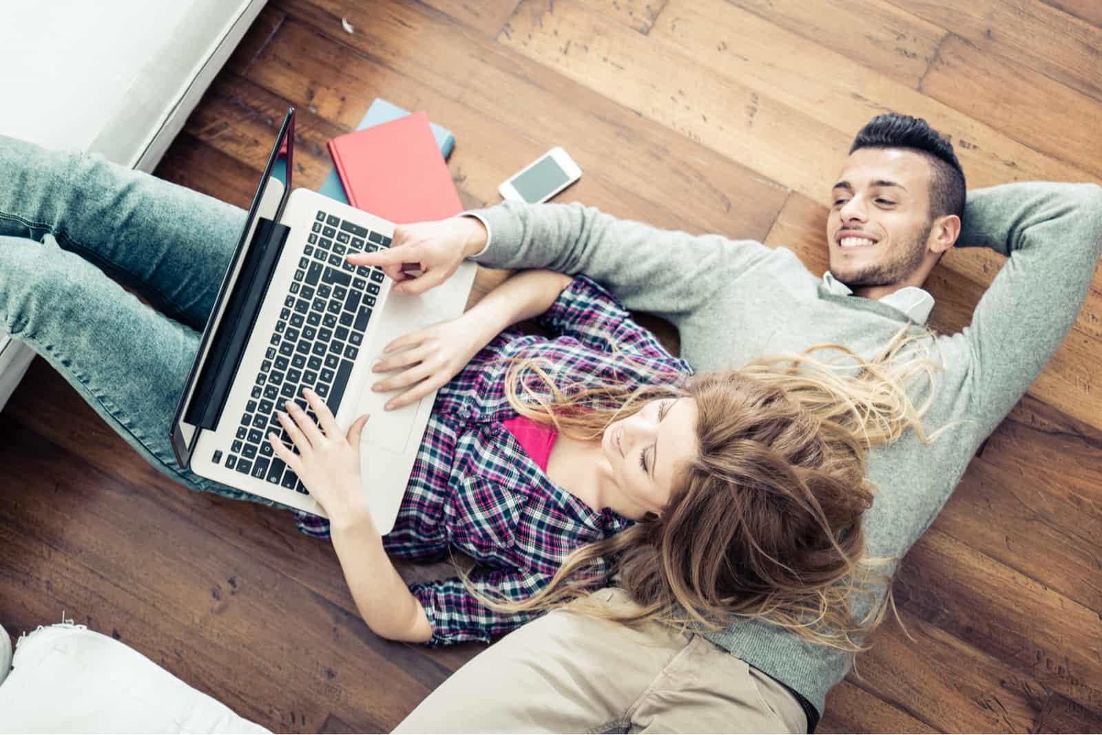 Auf dem Boden des Raumes schaut sich ein Liebespaar etwas auf einem Laptop an