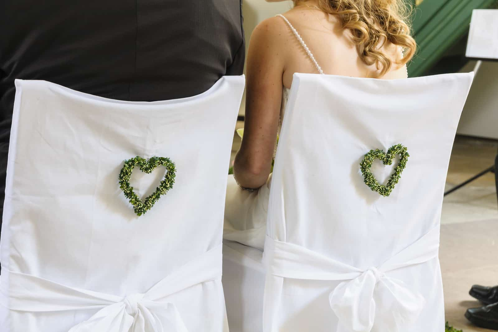 Braut und Bräutigam sitzen auf Hochzeitsstühlen