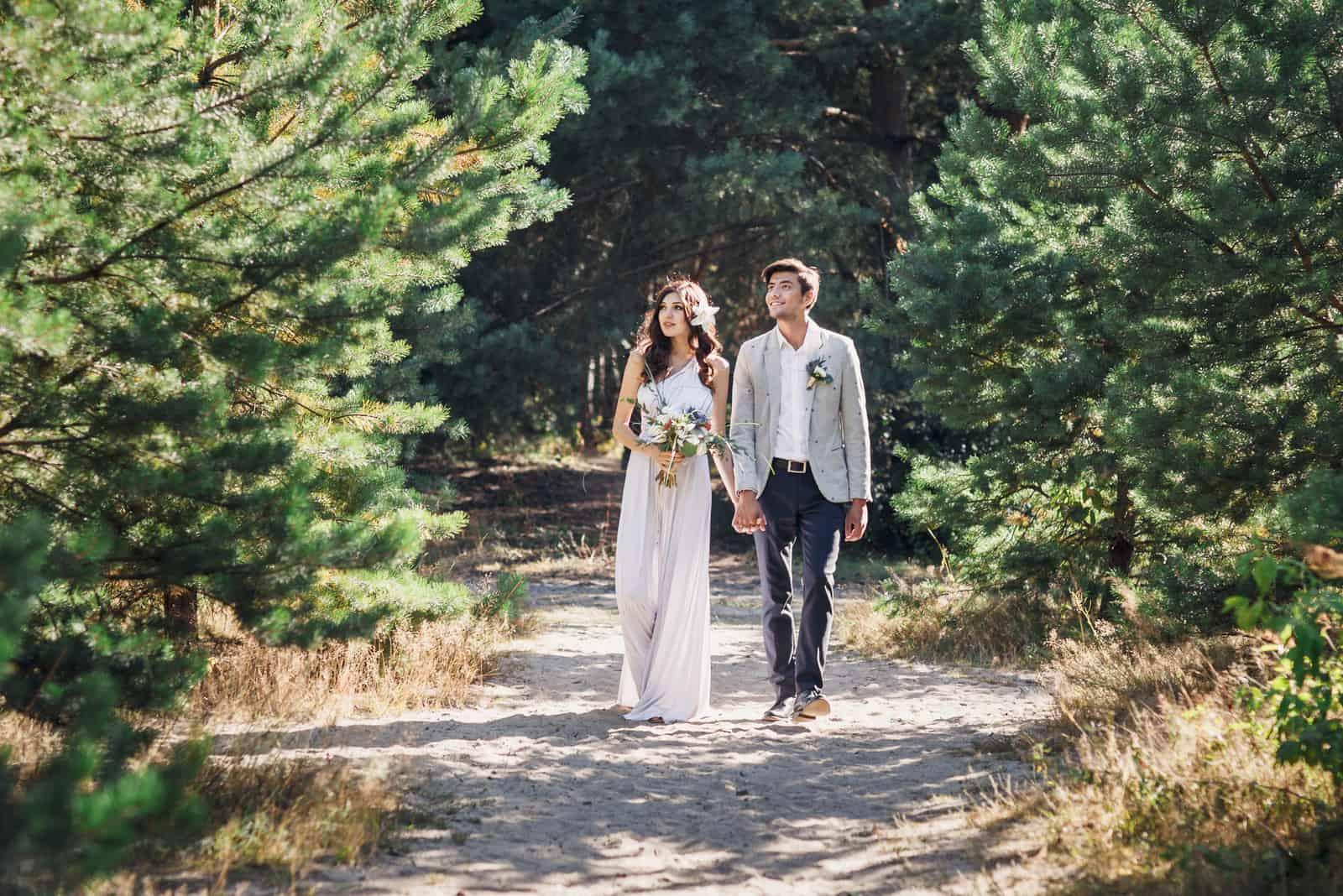 Das Brautpaar geht Händchen haltend durch den Wald
