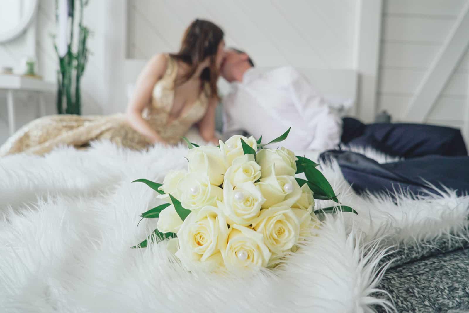 Das Brautpaar küsst sich auf dem Doppelbett