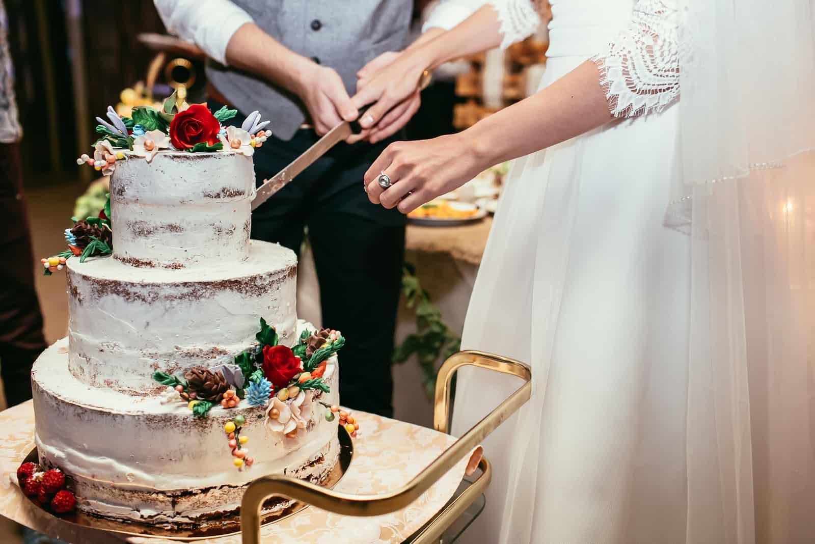 Das Brautpaar schnitt eine schöne weiße Hochzeitstorte