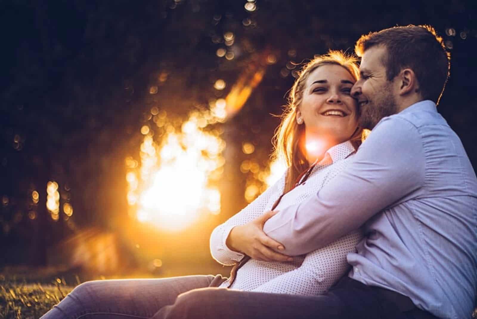 Das Paar umarmt sich bei Sonnenuntergang im Wald