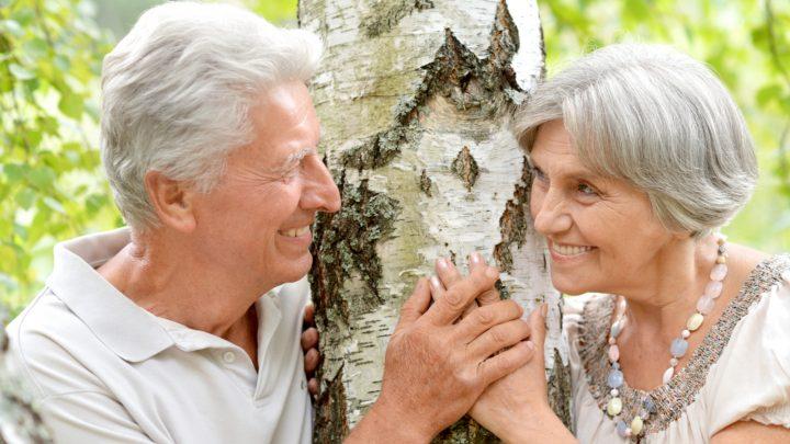 neben der Birke steht ein lächelndes glückliches älteres Liebespaar