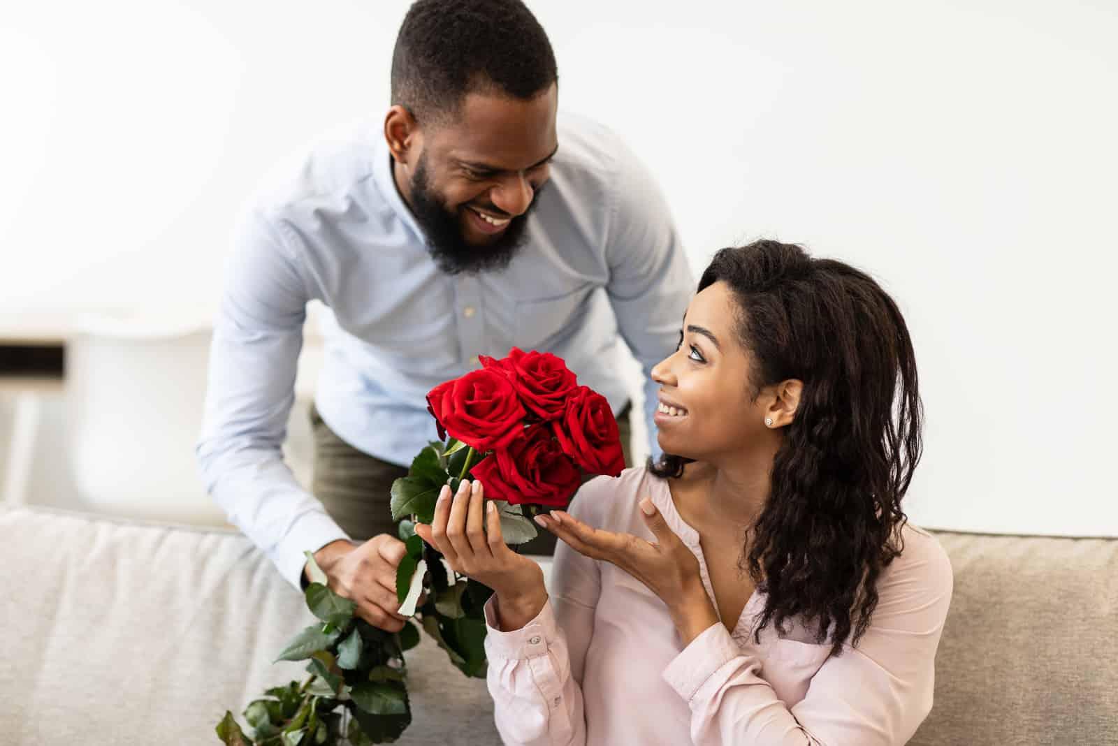 Der Ehemann gibt der glücklichen Frau einen Strauß roter Rosen