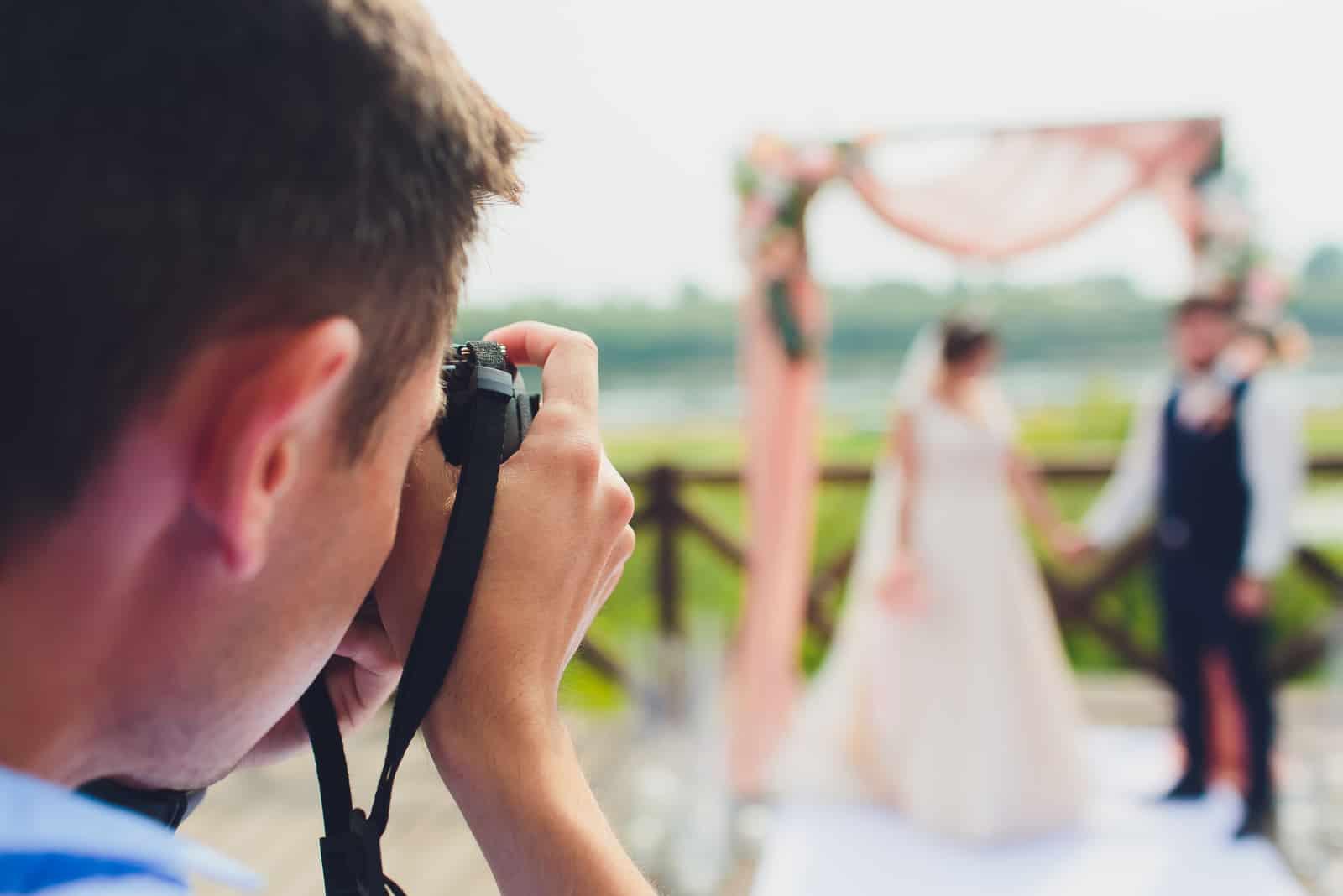 Der Fotograf fotografiert die Hochzeit des Brautpaares