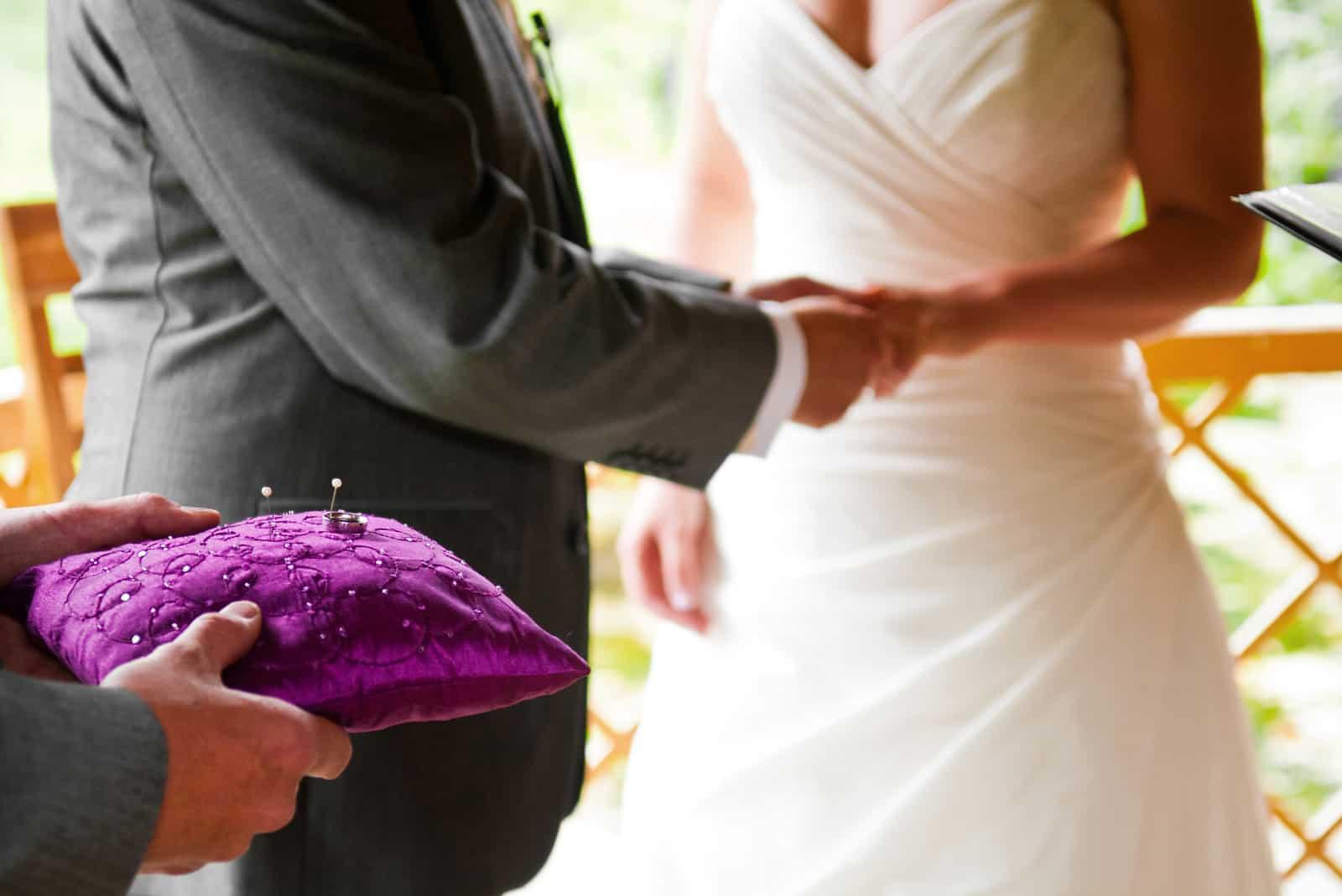 Der beste Mann hält den Ring vor das Brautpaar