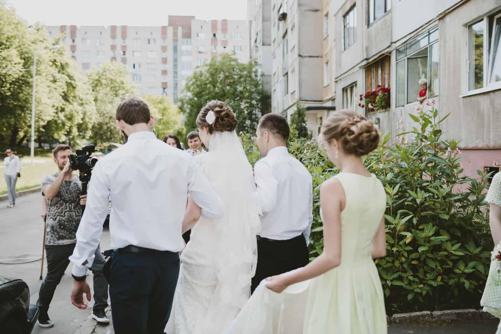 Die Braut mit den Trauzeugen geht zum Auto