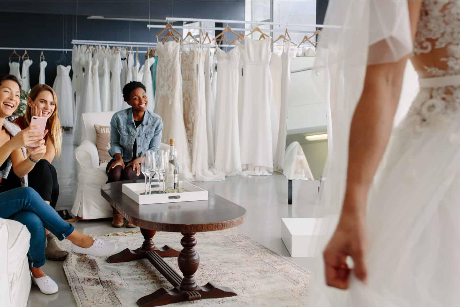 Die Braut und ihre Freunde wählen ein Hochzeitskleid