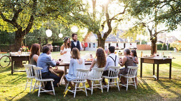 Jungvermählten und Gäste bei einem Hochzeitsessen im Garten