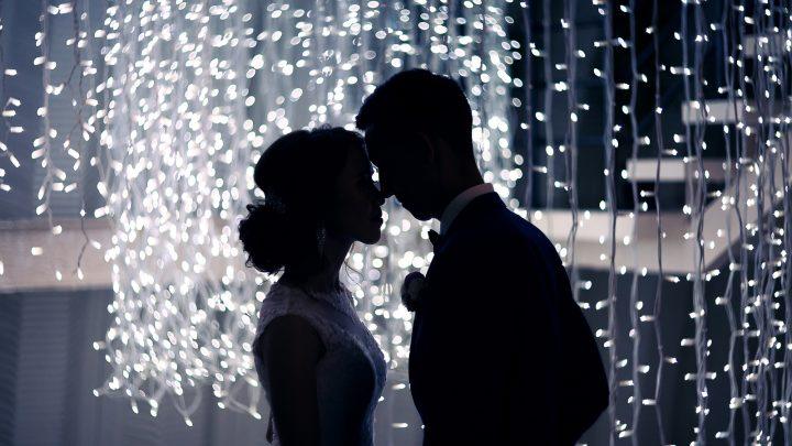 Die Jungvermählten küssen sich im Dunkeln mit Ledlight-Dekorationen