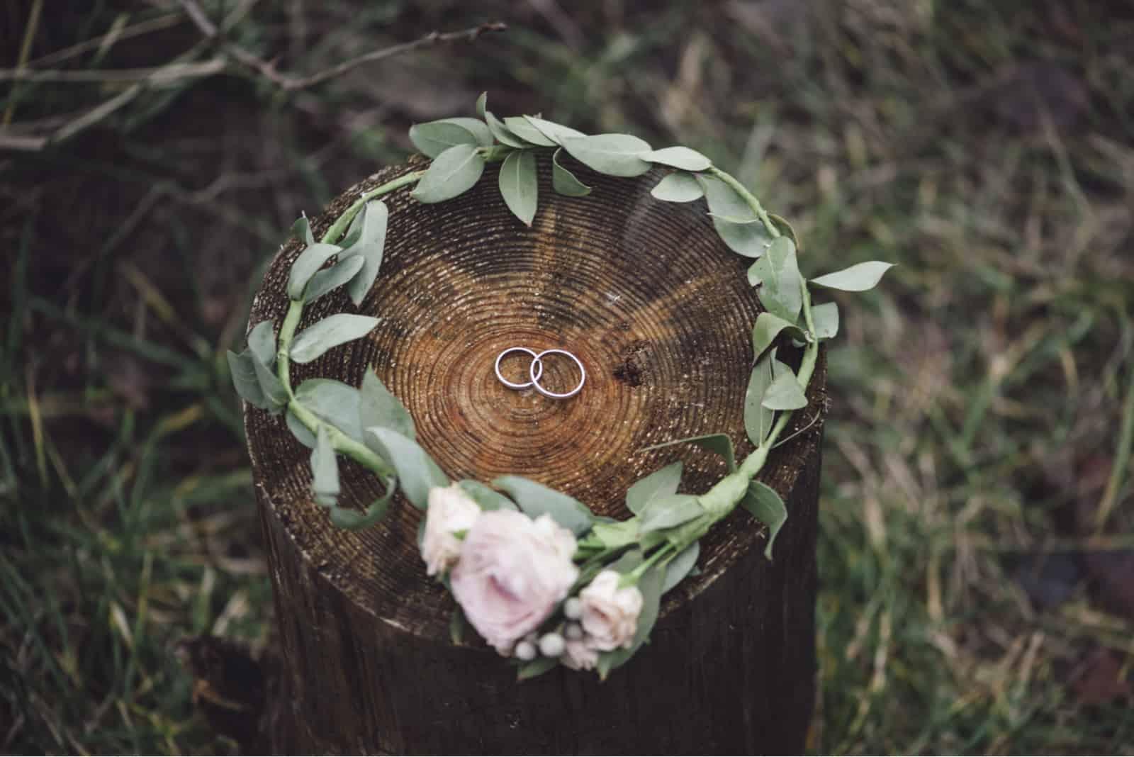Eheringe auf einem Baum in einem Blumenkranz