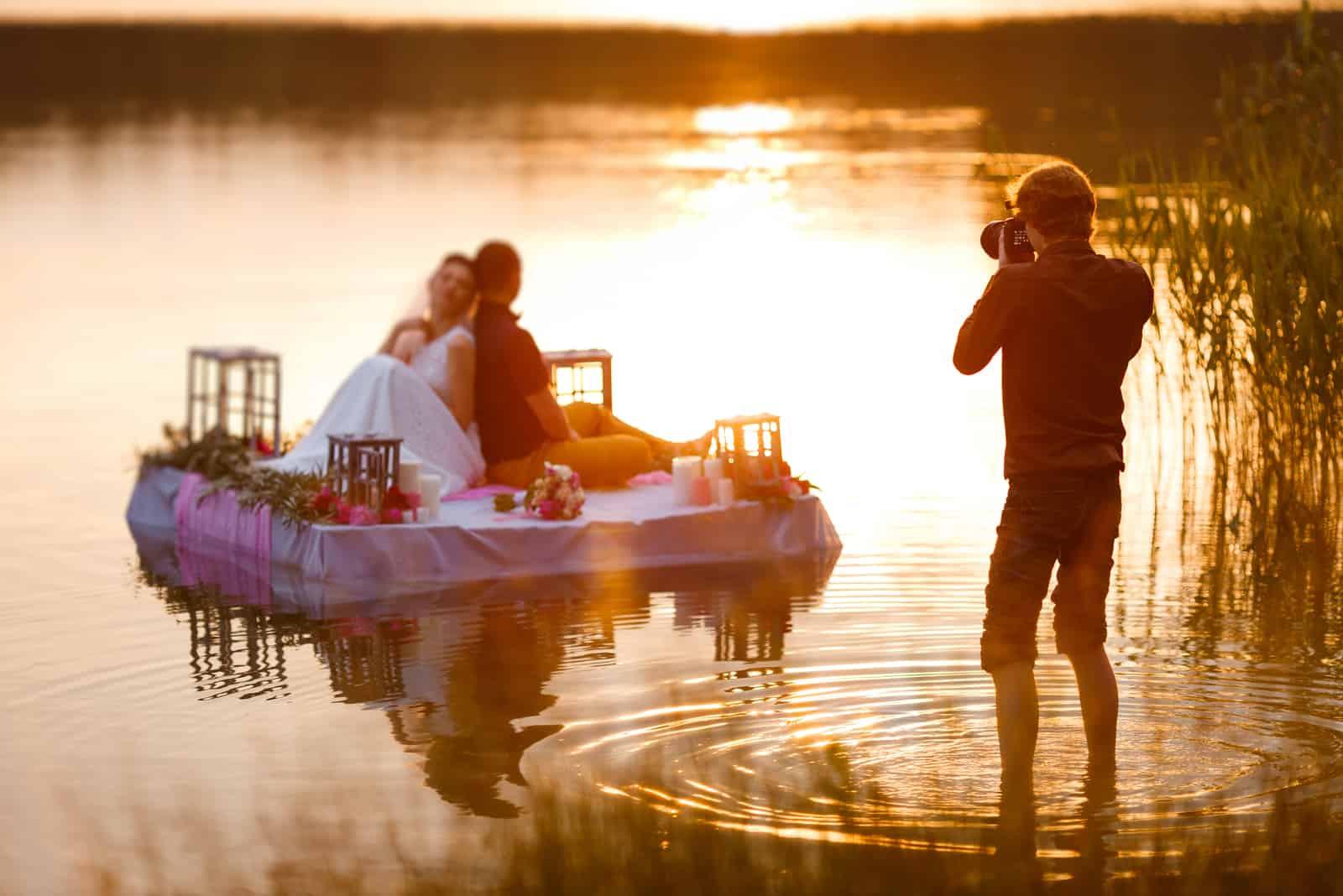Ein Hochzeitsfotograf fotografiert das Brautpaar auf einem Floß im See
