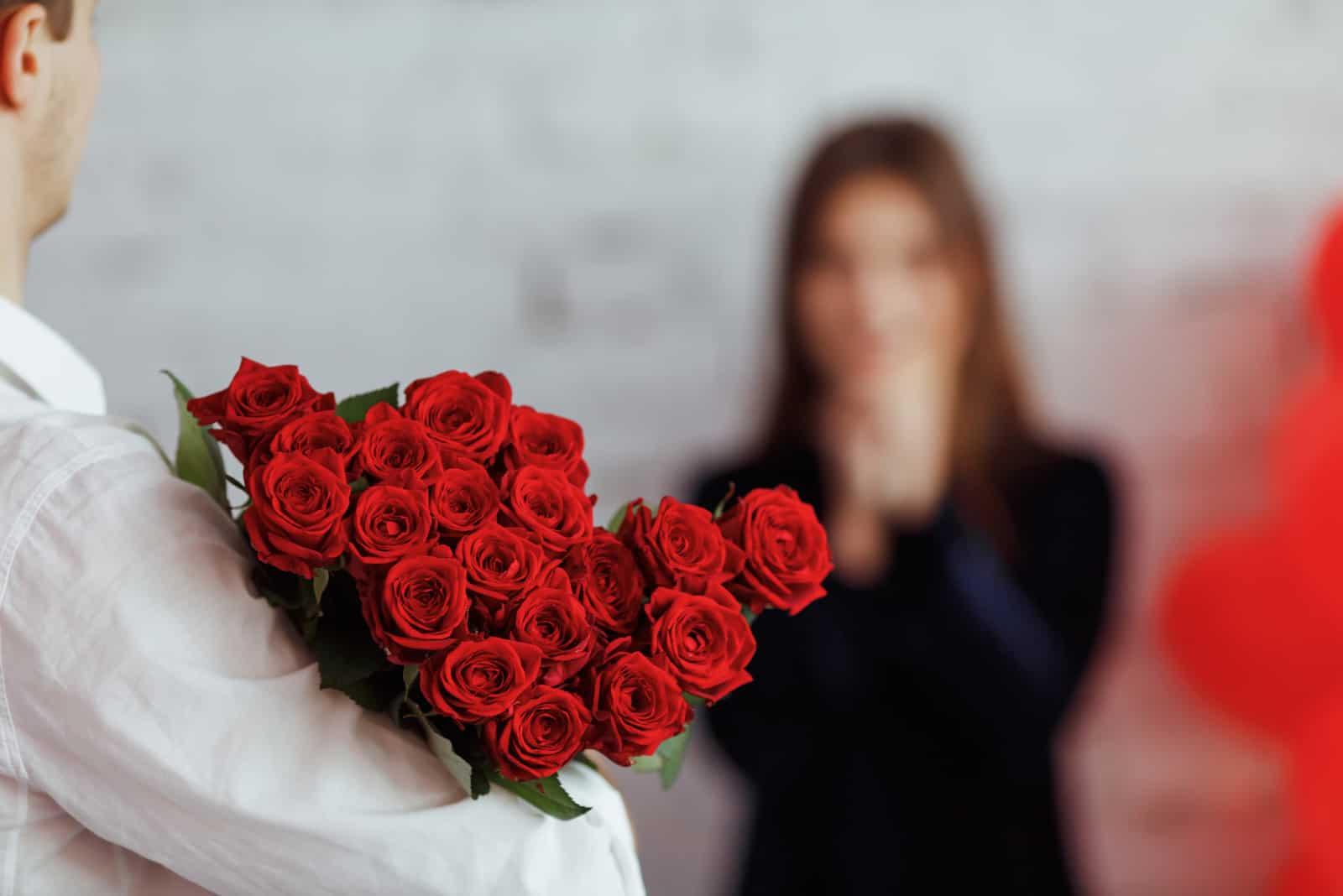 Ein Mann präsentiert eine überraschte Frau mit einem großen Strauß roter Rosen