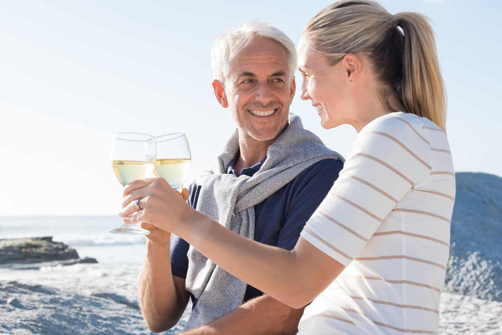 Ein älteres Liebespaar am Strand röstet mit Wein