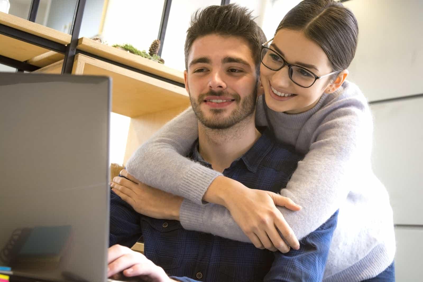 Ein lächelndes Liebespaar macht etwas auf einem Laptop