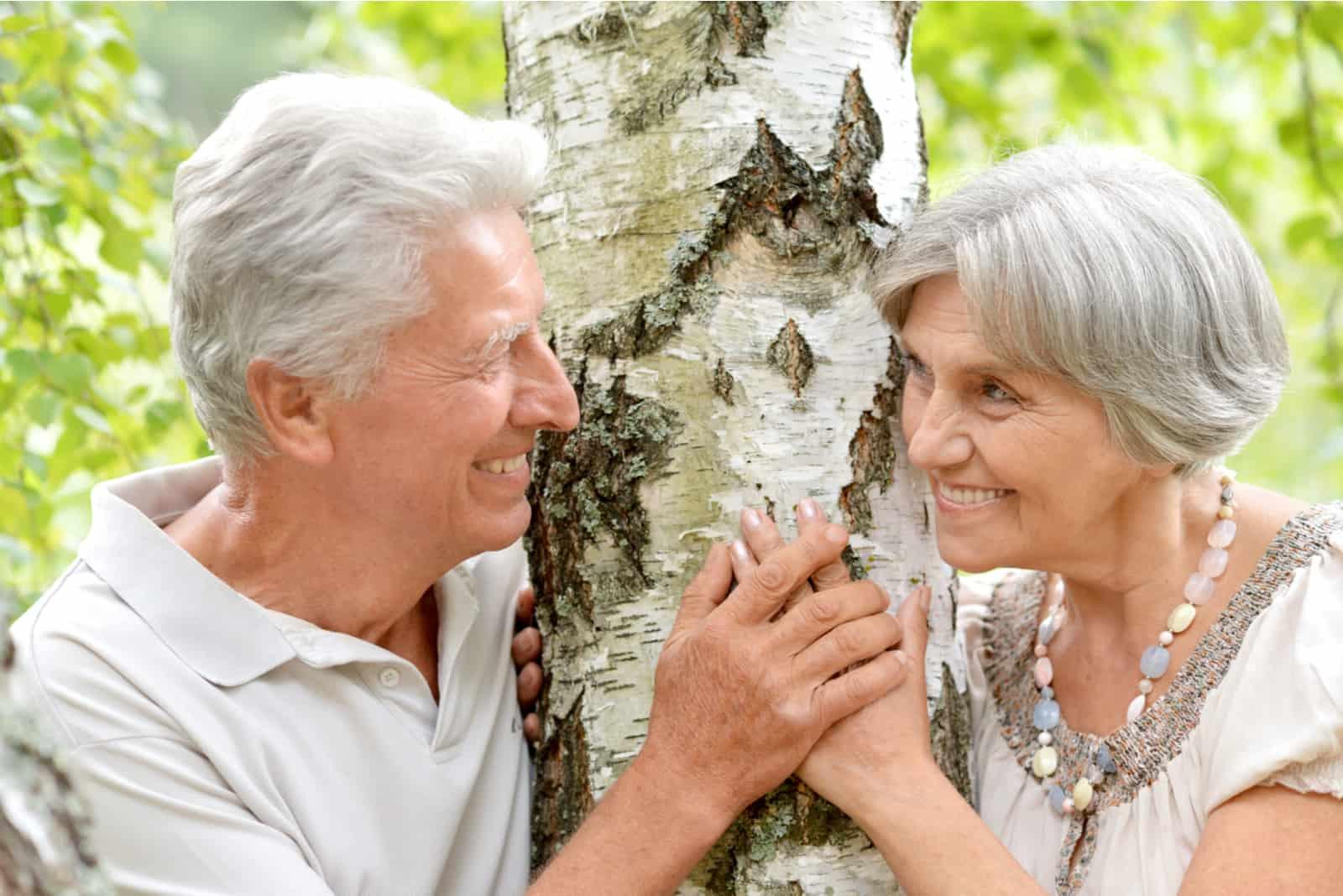 Ein verliebtes älteres Ehepaar steht neben einer Birke
