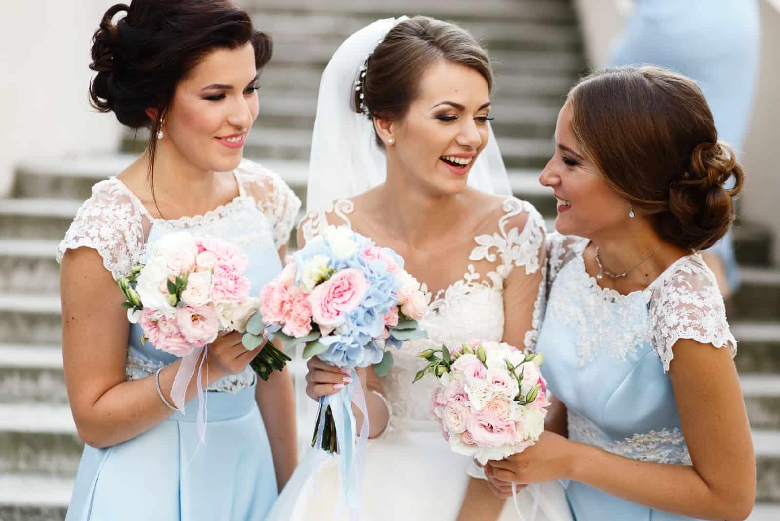 Eine schöne Braut steht mit den Brautjungfern auf der Treppe