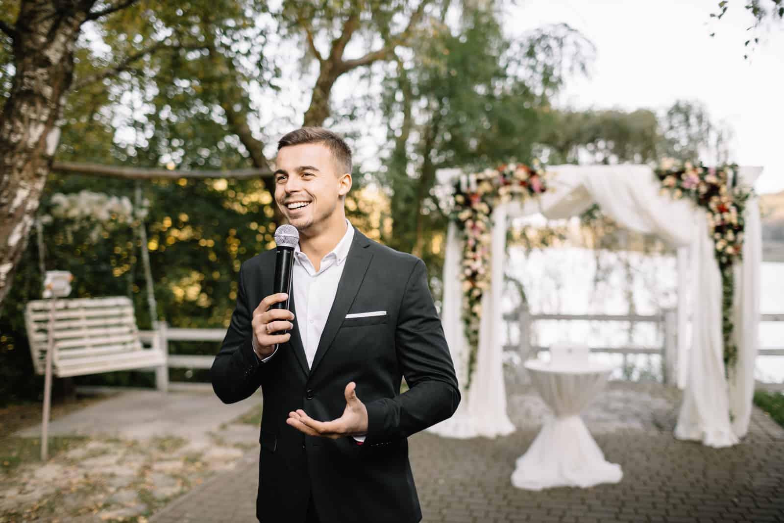 Eleganter Mann mit einem Mikrofon, das Rede spricht
