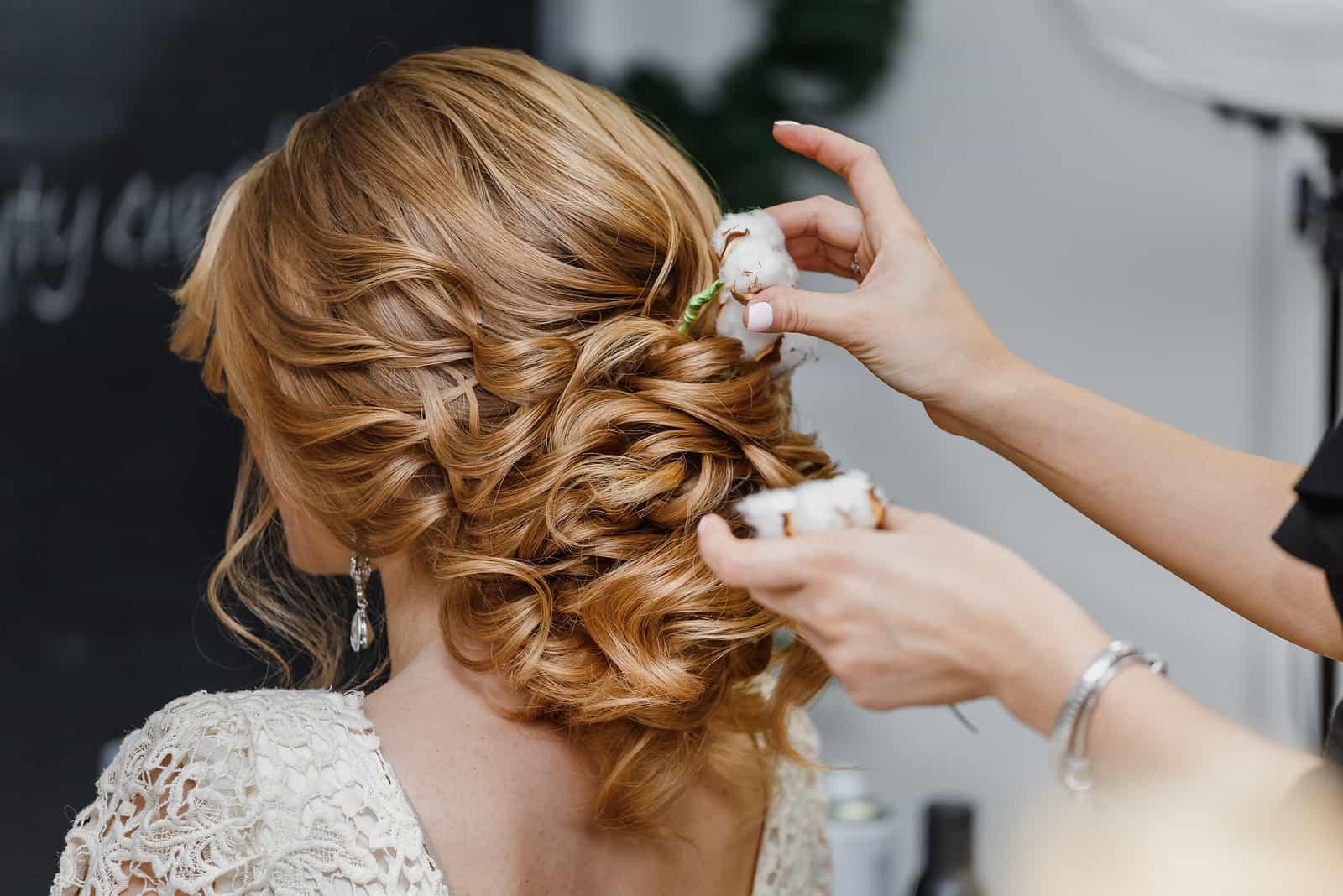 Florist macht die Braut eine Hochzeitsfrisur