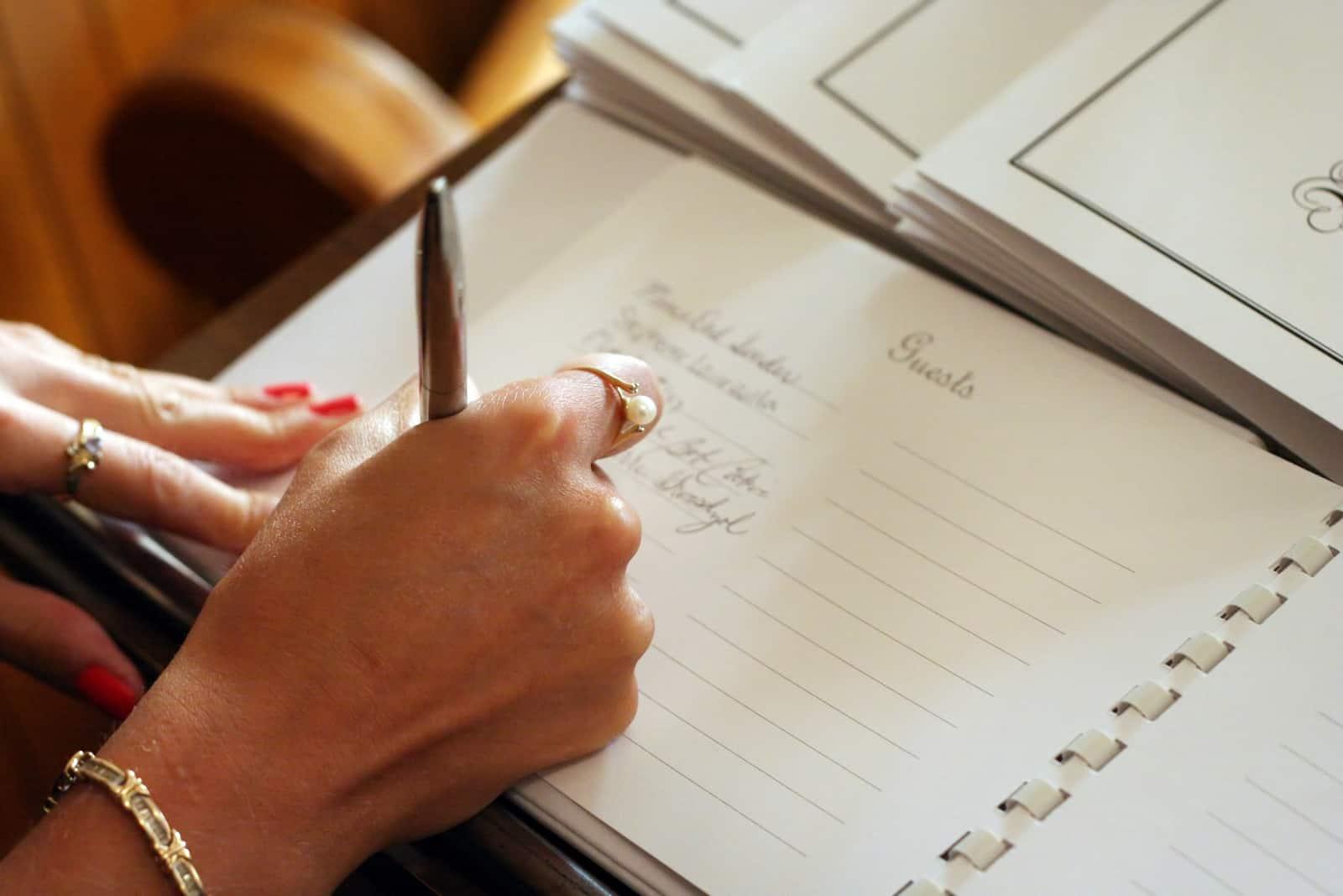 Frauenhand, die ein Gästebuch mit einem Stift signiert