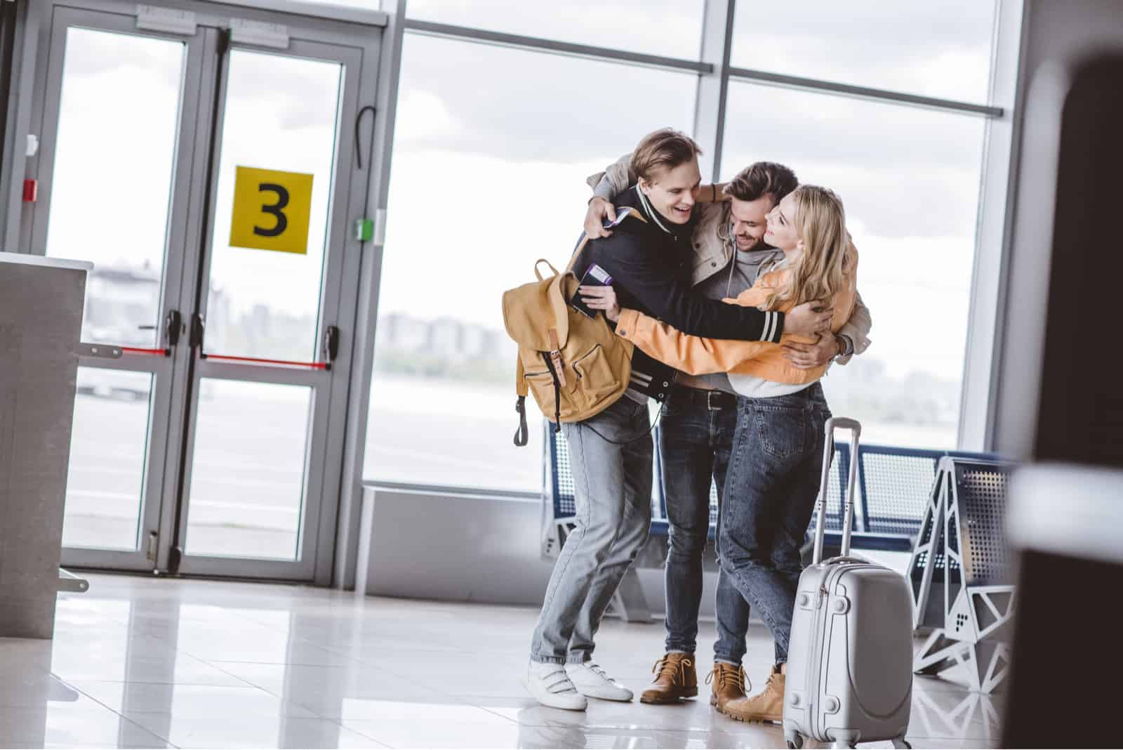 Freunde am Flughafen umarmen