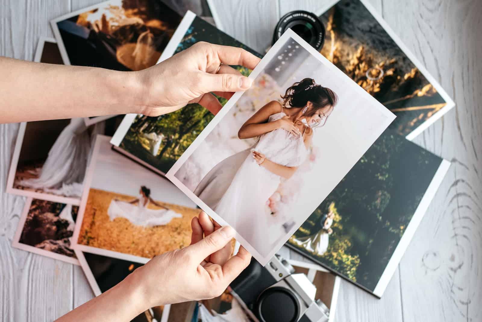 Gedruckte Hochzeitsfotos mit Braut und Bräutigam, einer schwarzen Vintage-Kamera und Frauenhänden mit Foto