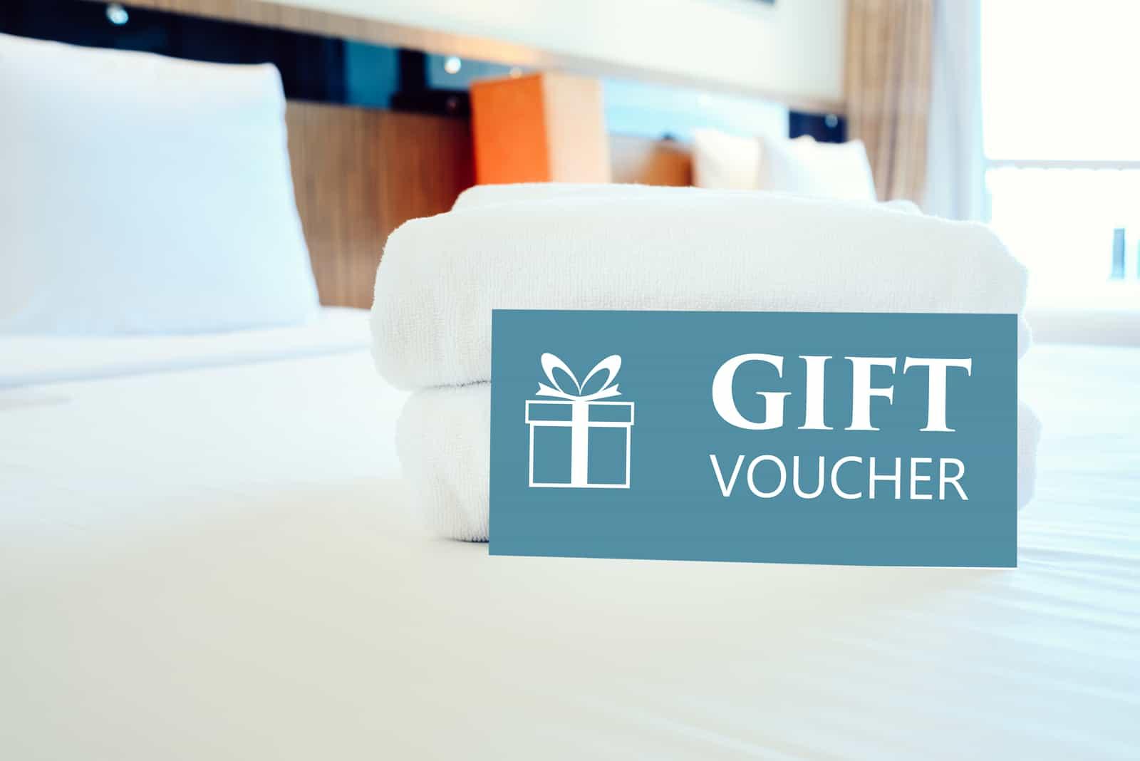 Geschenkgutscheinkarte in einem Hotelzimmerbett mit weißem Handtuch.