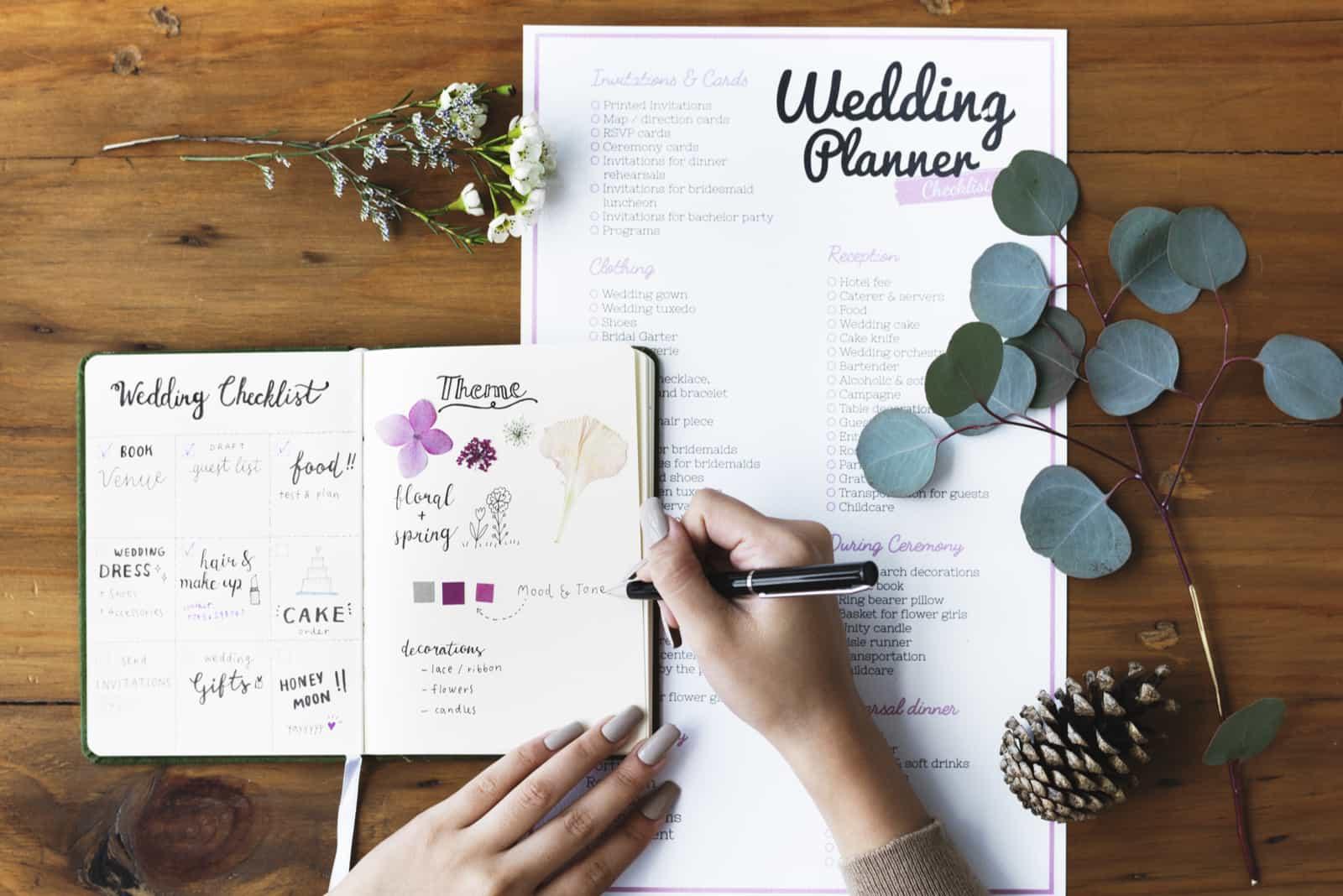 Hände, die auf Hochzeitsplaner-Notizbuch überprüfen
