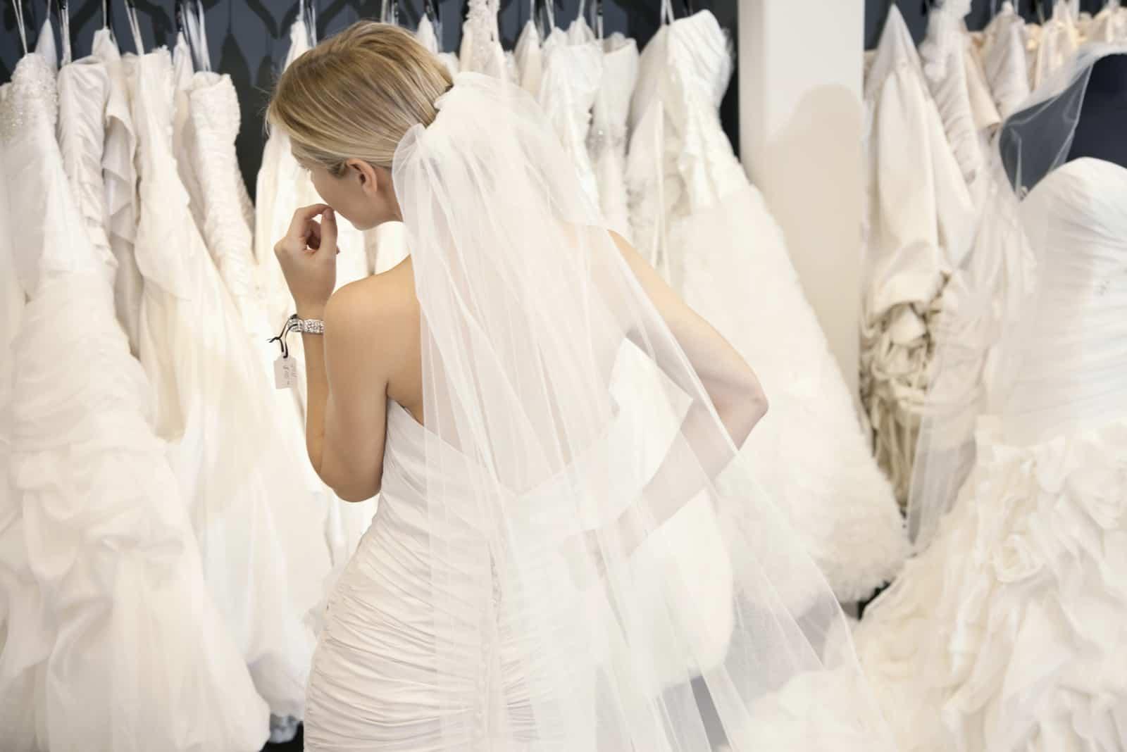 Hintere Ansicht einer jungen Frau im Hochzeitskleid, die Brautkleider auf Anzeige in der Boutique betrachtet
