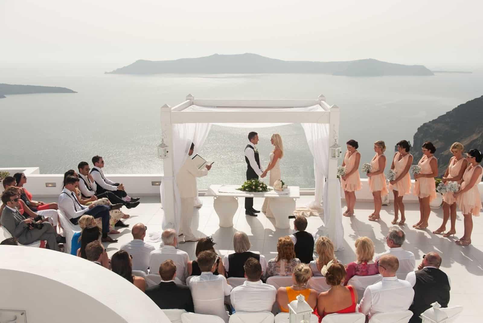 Hochzeit auf einer schönen Terrasse am Meer halten die Jungvermählten Händchen