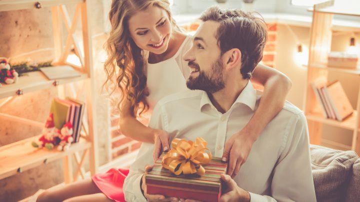 Eine lächelnde Blondine gibt einem Mann ein Geschenk