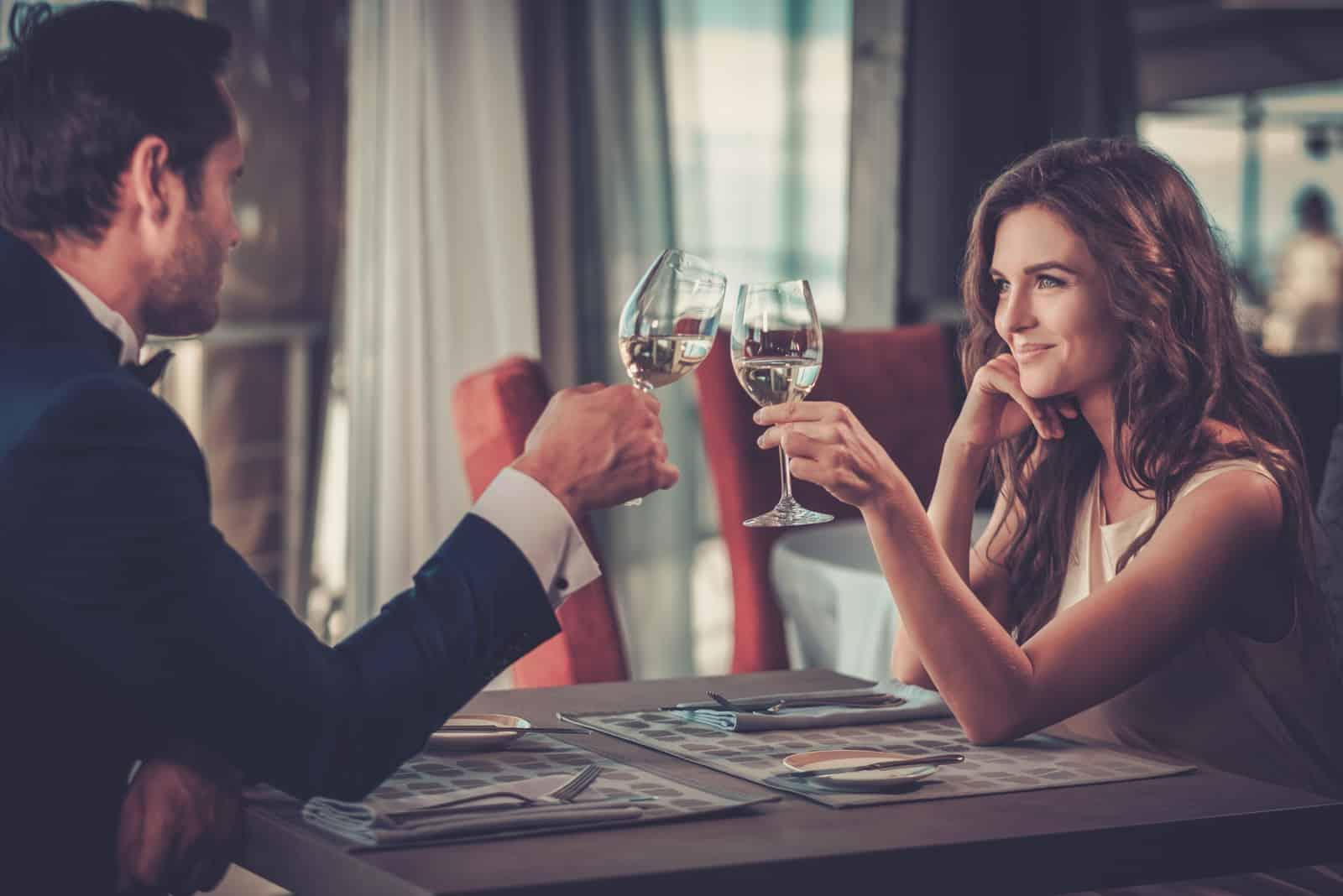Im Restaurant röstet ein schönes Paar mit Wein