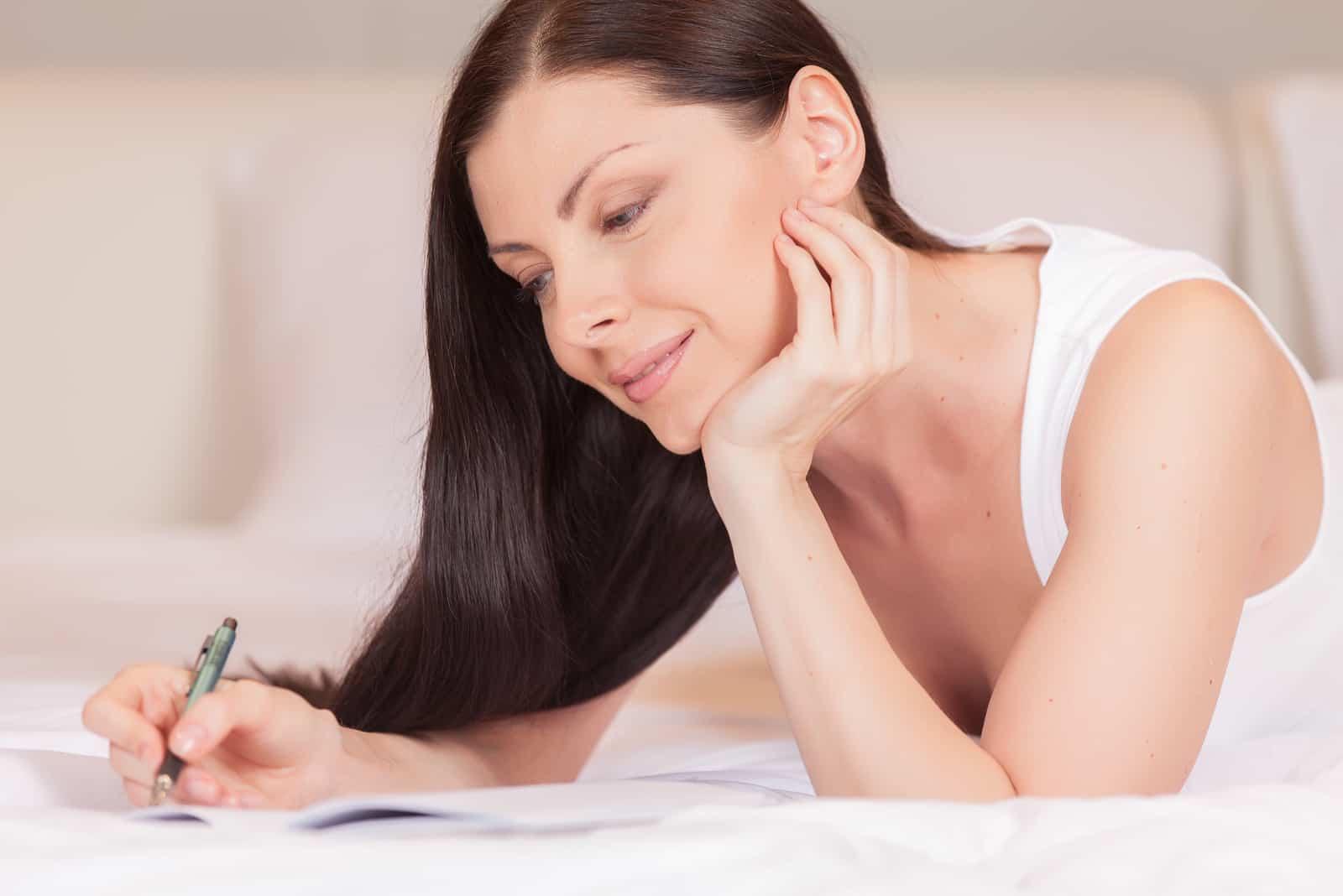 Mädchen schreibt Tagebuch, während es morgens im Bett liegt. schöne Brünette, die im Bett ruht und Brief schreibt
